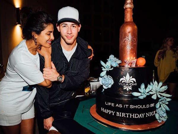Priyanka Chopra and Nick Jonas pose with the latter's big birthday cake